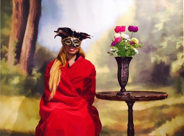 Africah dressed in a red velvet cloak and masquerade mask for a 19th Century Photoshoot.