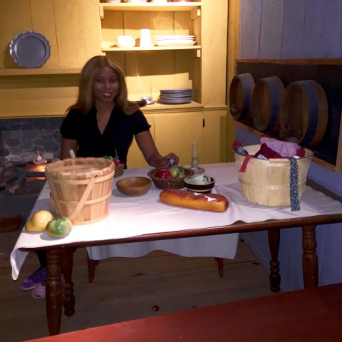 Africah sitting in the Pioneer's Kitchen. The table is set with the basic foods that was eaten during that time.